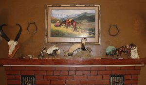Taxidermied ferret on mantle of fireplace