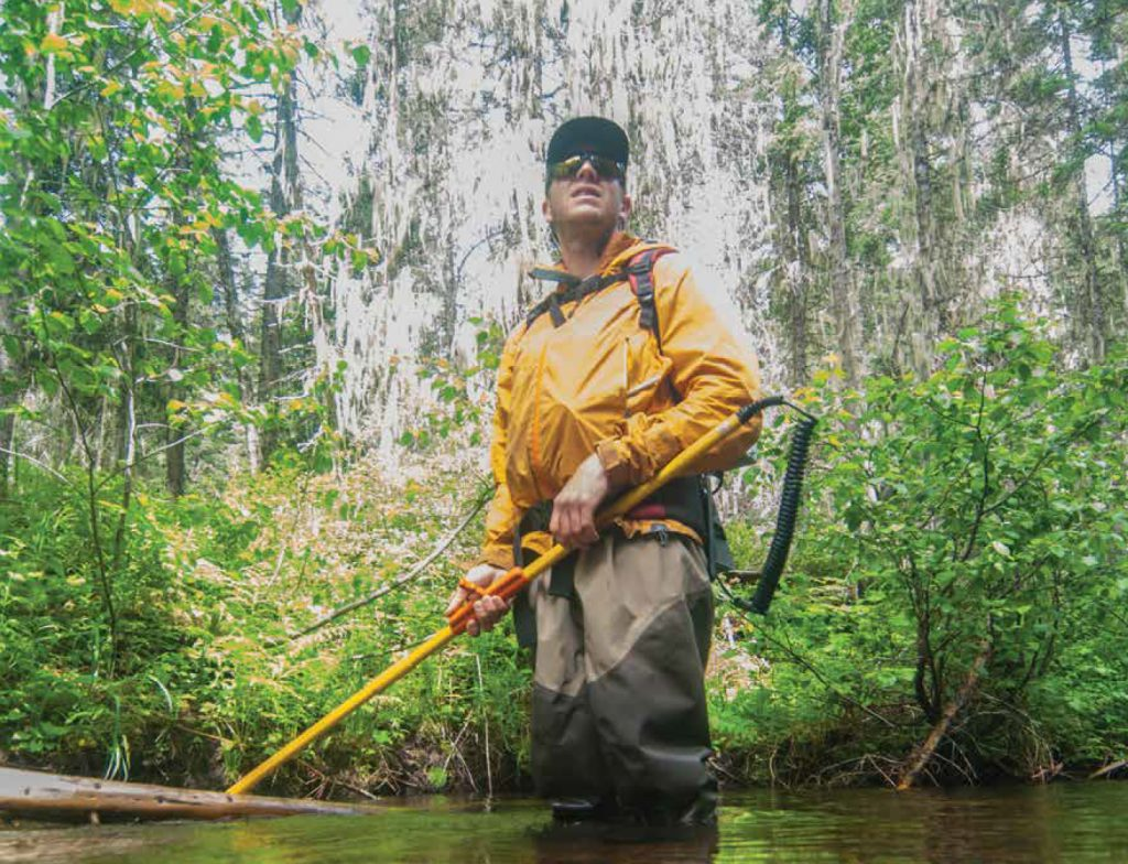 Sam Bourret, biologist with Montana Fish, Wildlife, and Parks, in a yellow jacket standing in a stream.