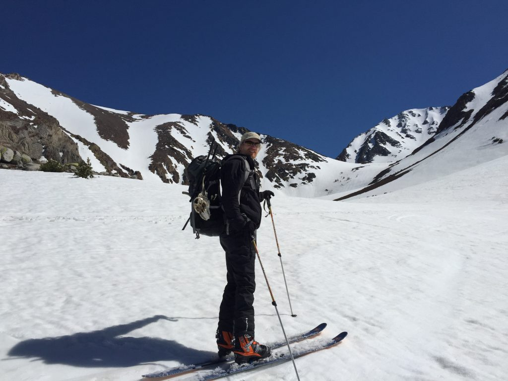 Photo of man in backpack skiing in high, snowy mountains with rock cliffs beyond