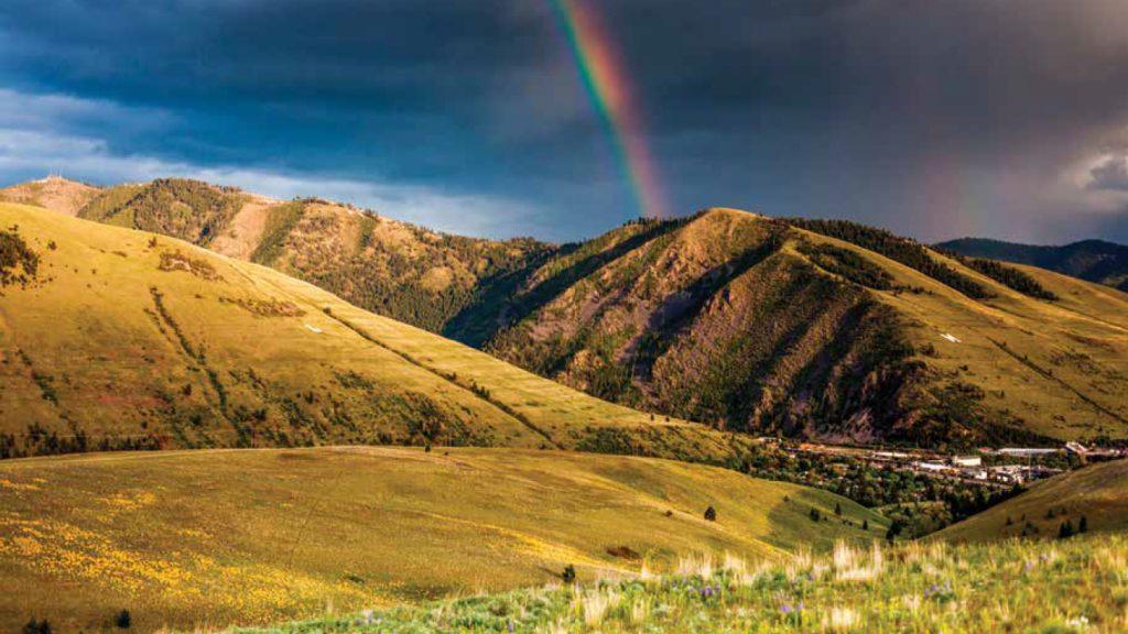 Rainbow over grassy hills