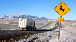truck driving on I-80 with deer sign