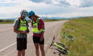 two people stopped on roads with bikes on ground holding animal