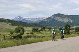 two people riding bikes with mountains behind