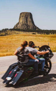 two people on motorcycle ride past devils tower